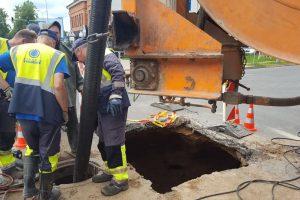 Šiaulių miesto gatvių sankryžoje atsivėrė duobė ir sukrito kelio danga